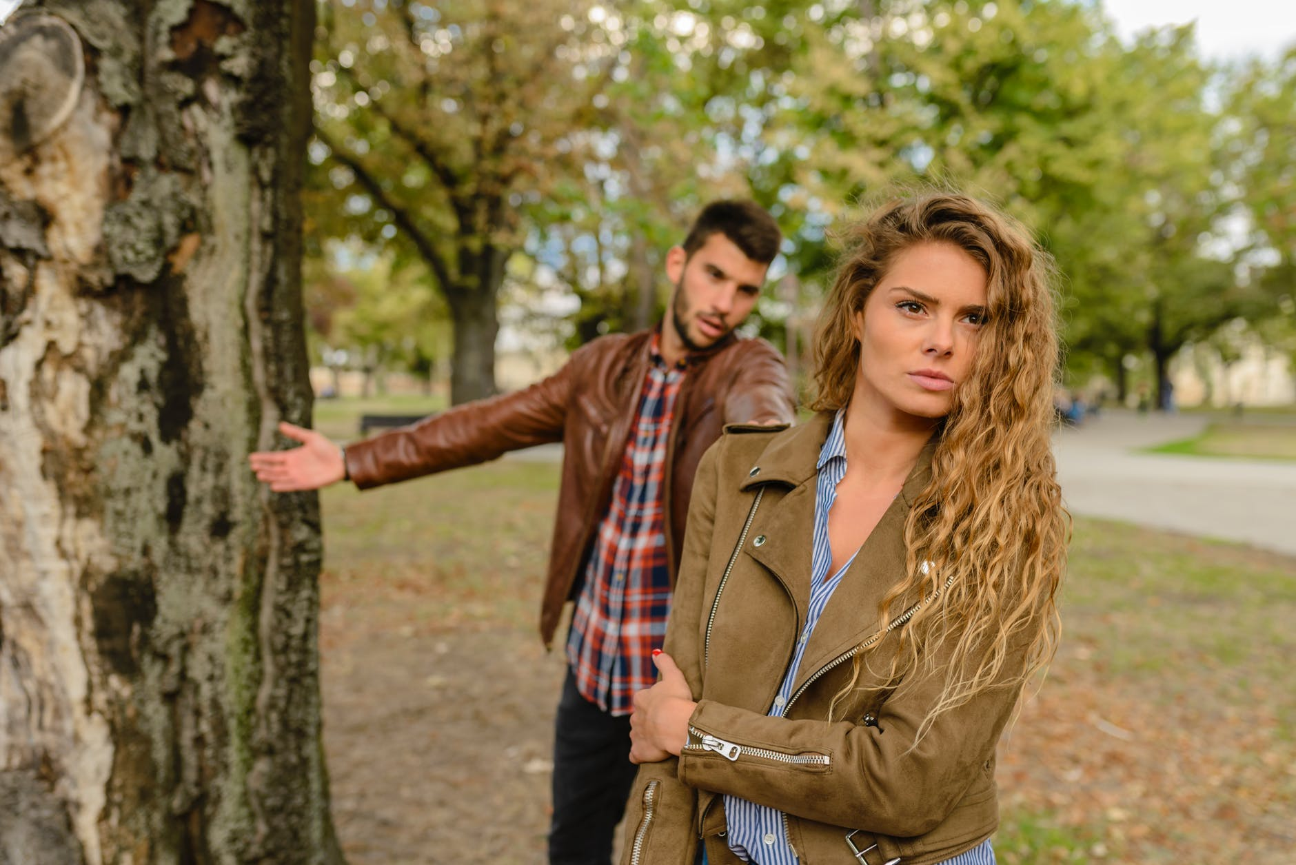 woman and man wearing brown jackets standing near tree
